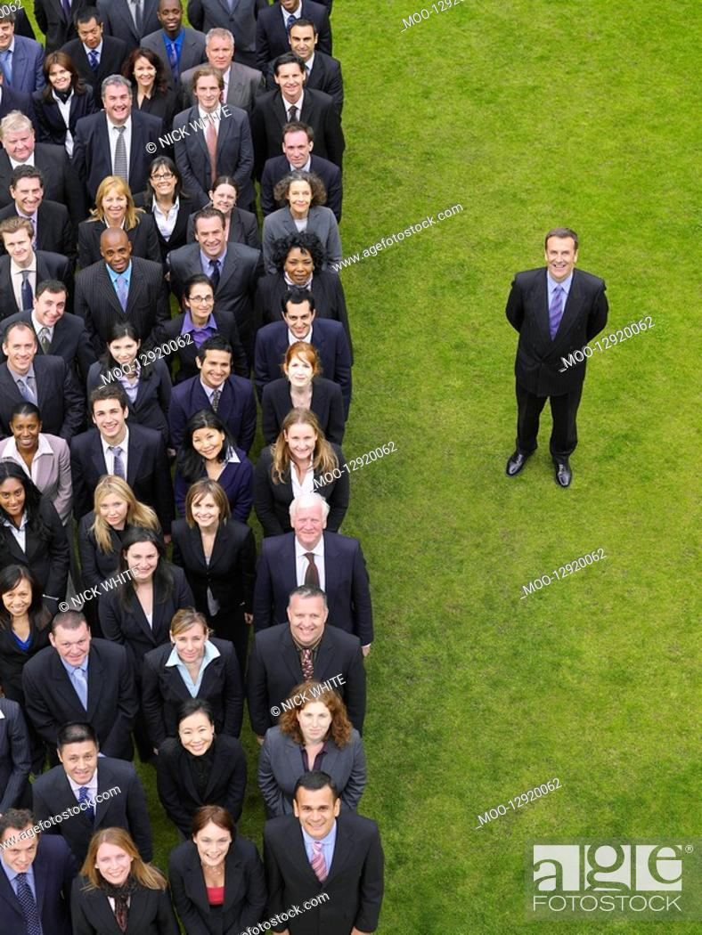 Stock Photo: Business man standing next to large group of business people in formation elevated view portrait.