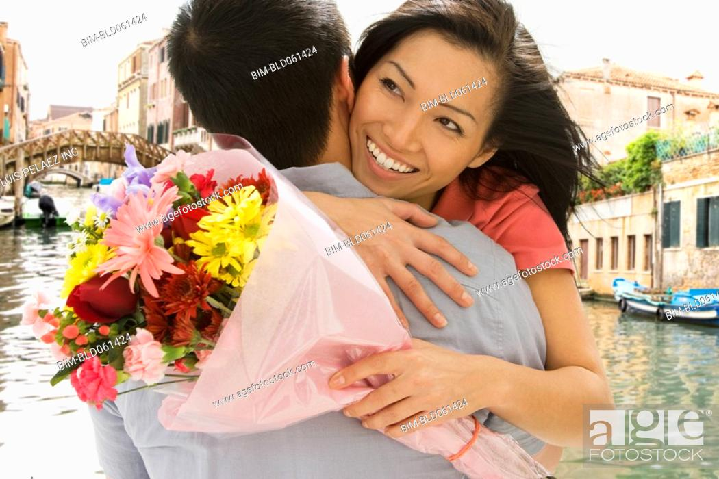 Stock Photo: Asian couple hugging with flowers.