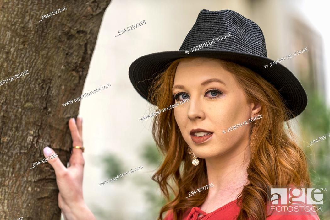 Stock Photo: Portrait of a 25 year old redheaded woman wearing a black hat in an urban setting.