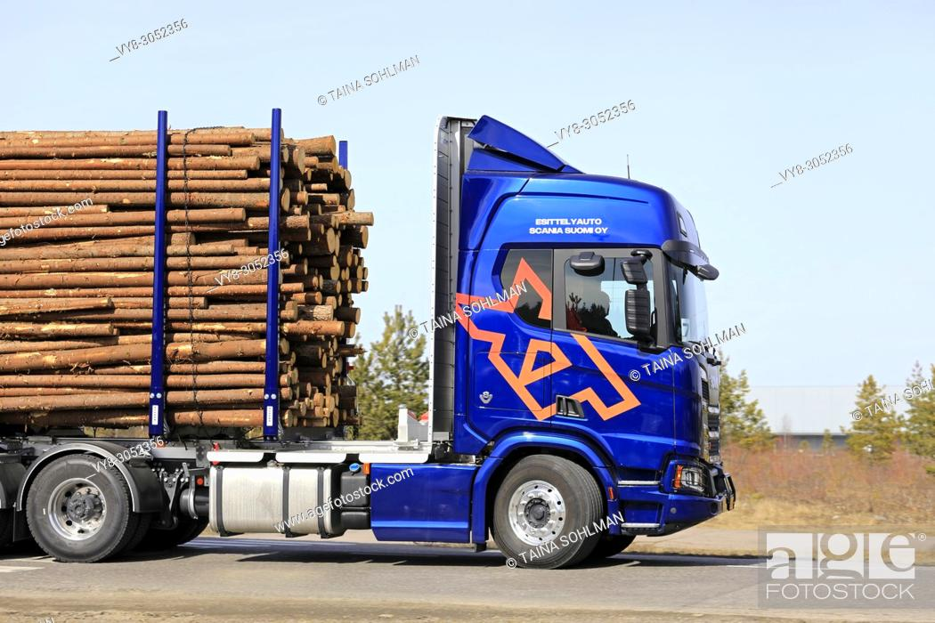 Stock Photo: Side view of blue Scania R730 XT logging truck at speed on the road during Scania Tour Turku 2018 in Lieto, Finland - April 12, 2018.