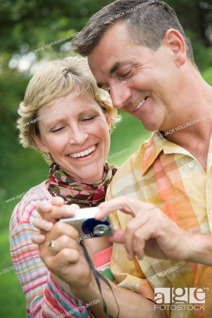 Stock Photo: Close-up of a mature couple looking at a digital camera and smiling.