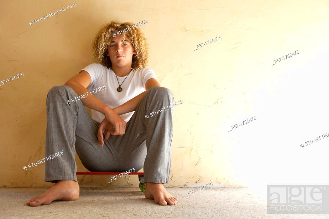 Stock Photo: Teenage boy sitting on his longboard.