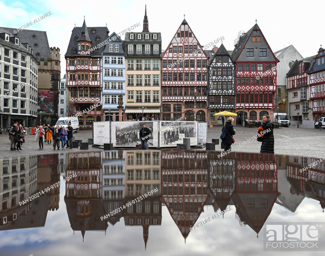 Stock Photo: 14 February 2020, Hessen, Frankfurt/Main: The half-timbered buildings of the Ostzeile on Frankfurt's Römerberg are reflected in a puddle of water.