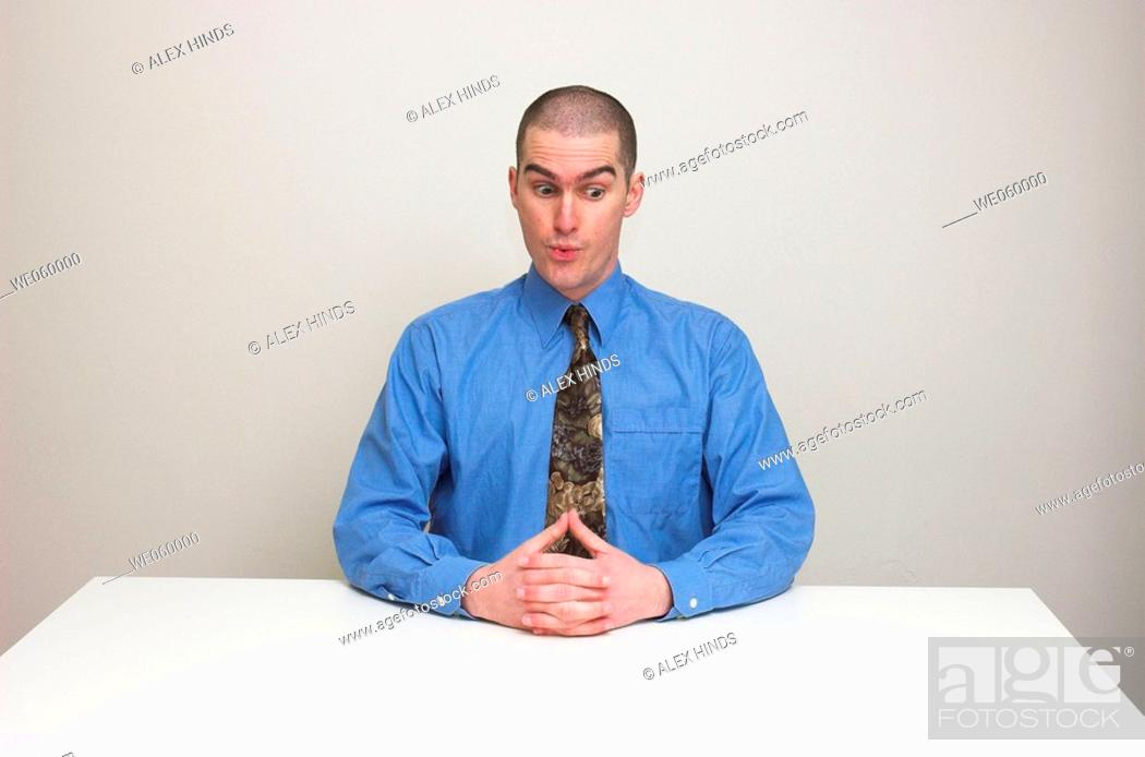 Stock Photo: Young man in business shirt and tie sitting at an empty desk. Expression suggests surprise and nervousness, at an unusual request perhaps.