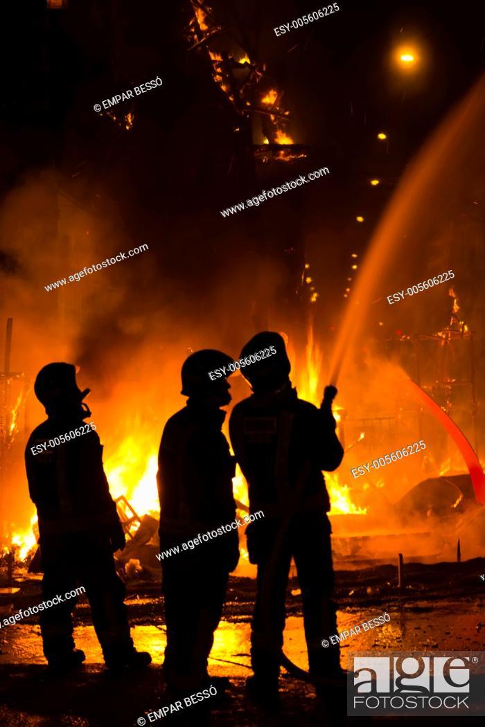 Stock Photo: Firemen controlling fire during the cremà, fallas festival. Valencia. Spain. 2013.