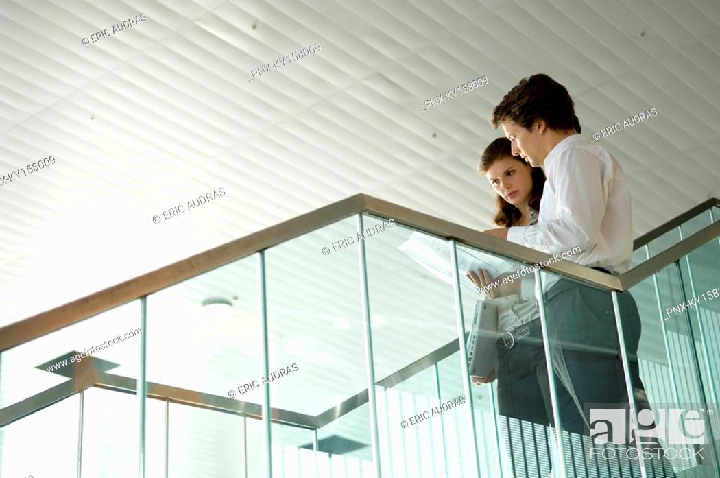 Stock Photo: Low angle view of a businessman and a businesswoman looking at a blueprint.