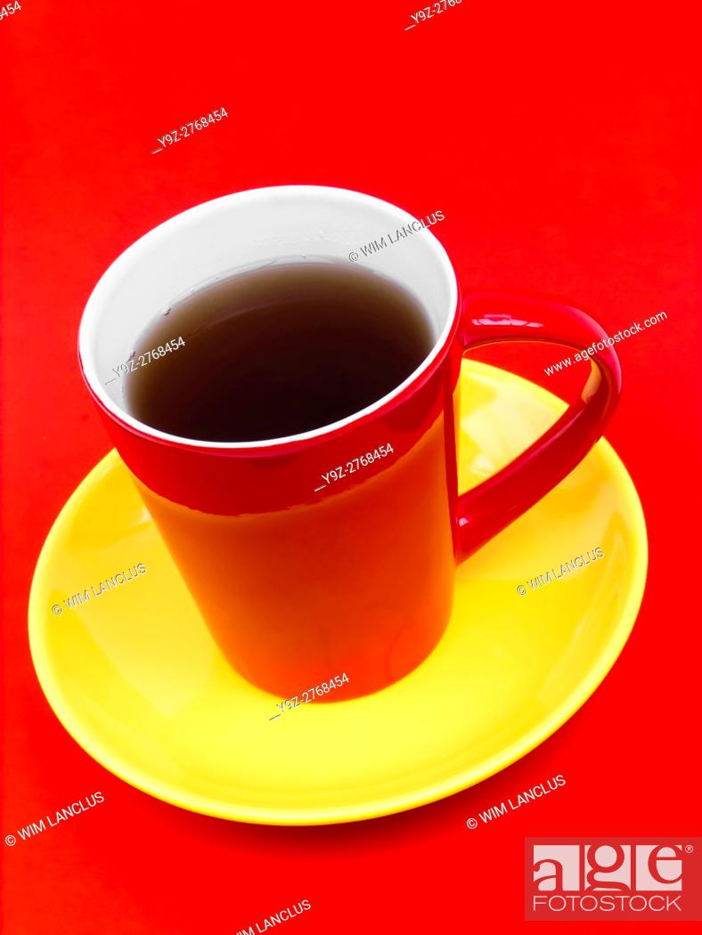 Stock Photo: Coffee in red cup on yellow saucer against red background, colors representing spanish flag.