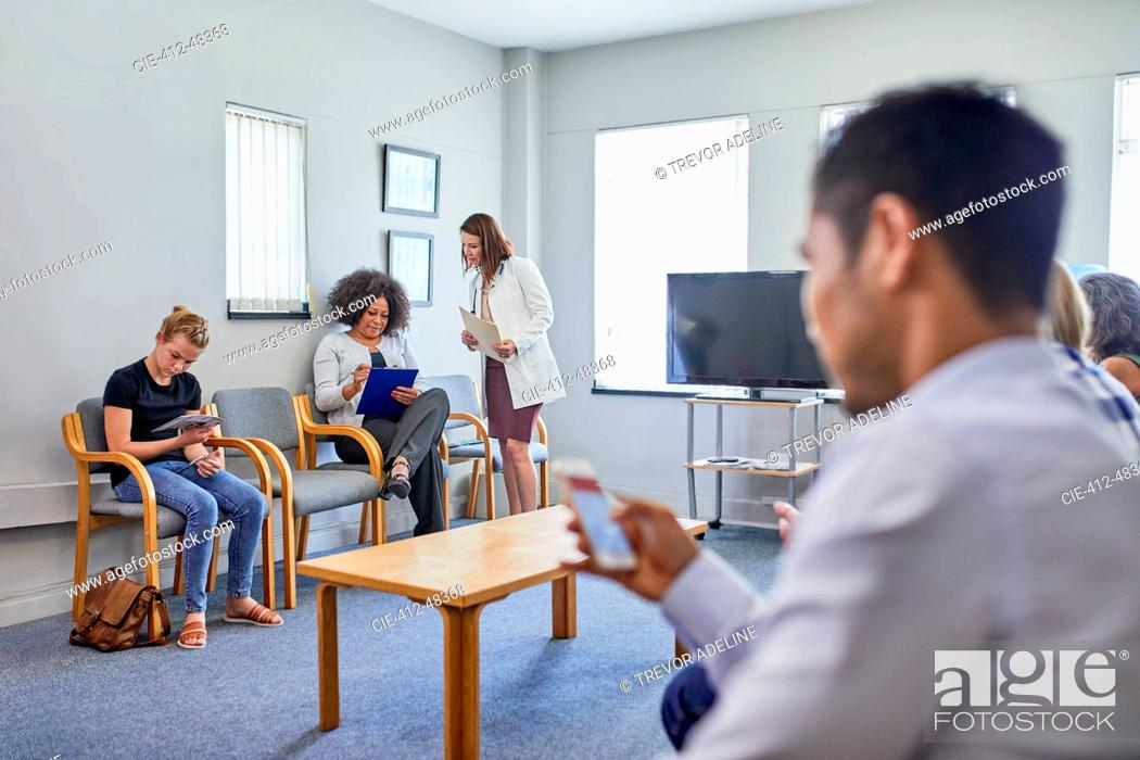 Stock Photo: Doctor and patients in clinic waiting room.