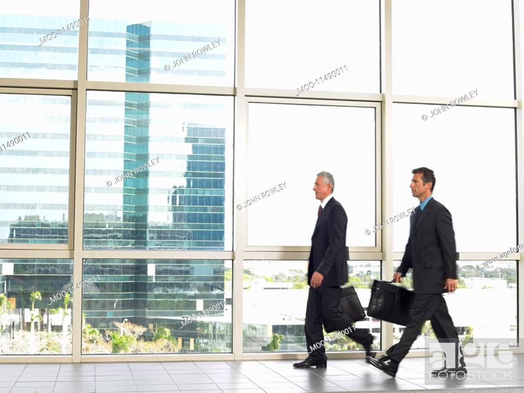 Stock Photo: Businessman walking by office window.