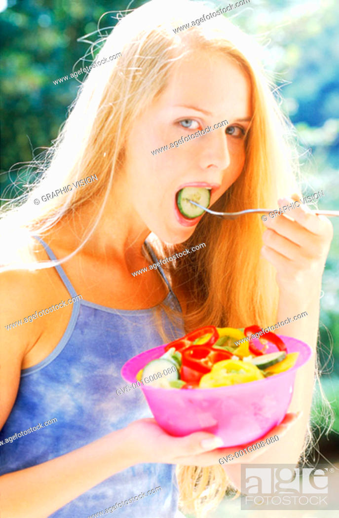 Stock Photo: A young woman eating a bowl of salad.