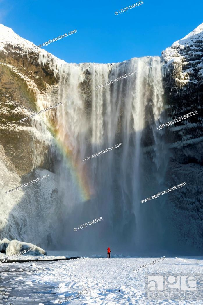 Stock Photo: A person wearing a red coat standing below Skogafoss waterfall in winter.