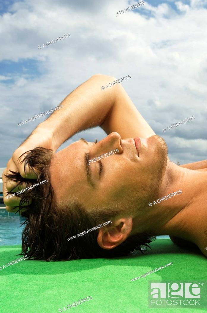 Stock Photo: Man sunbathing at the poolside.