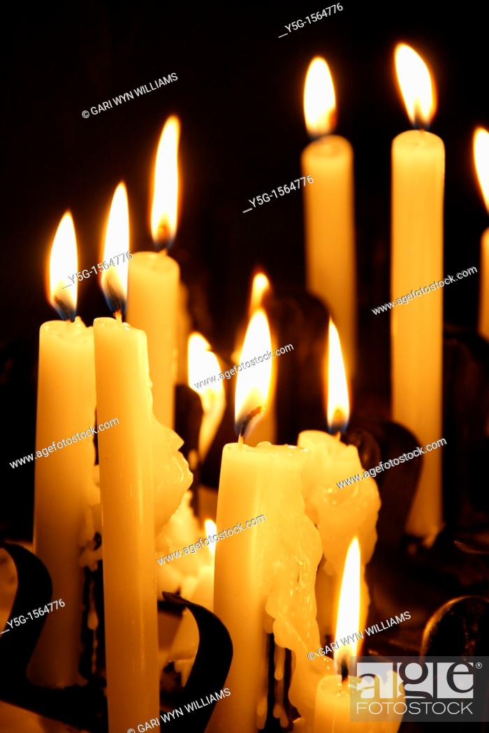 Stock Photo: many lit candles in dark room in church.
