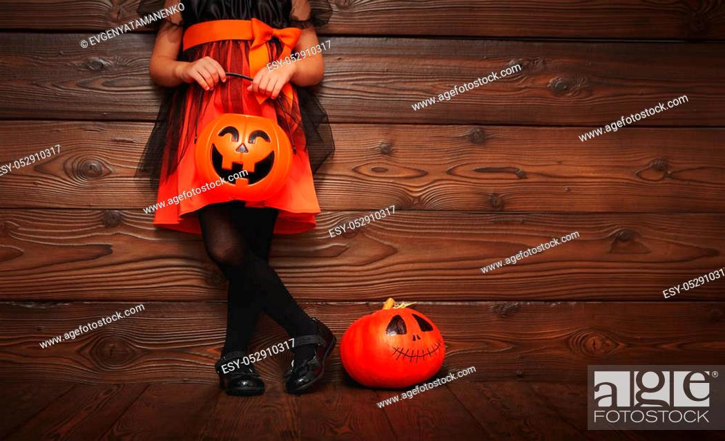 Stock Photo: legs of child girl in witch costume for Halloween with pumpkin Jack on a dark wooden background.