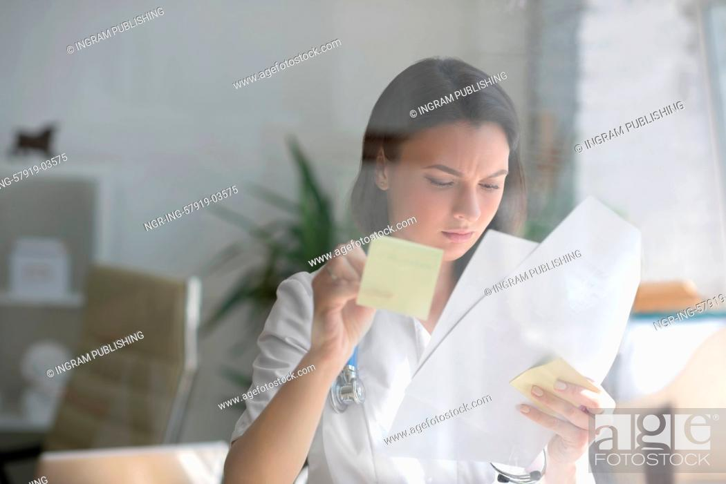 Stock Photo: Medical doctor writing patient test results on transparent board to diagnose.