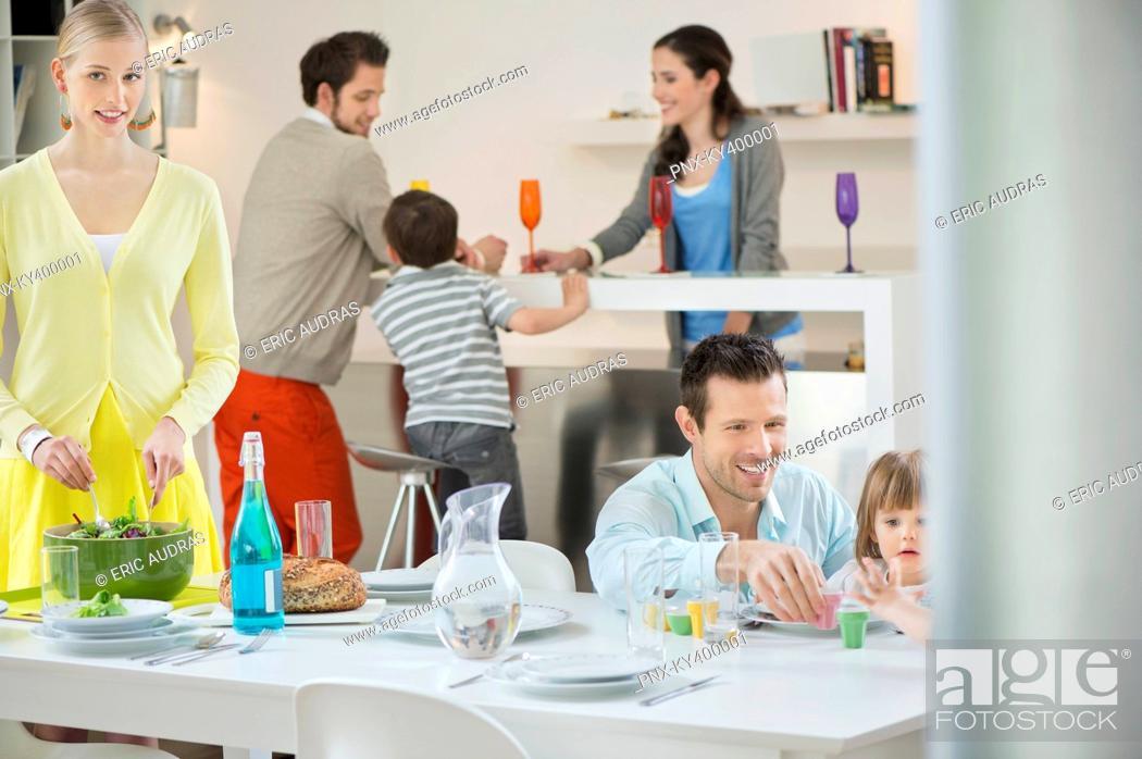 Stock Photo: Family setting table for dinner.
