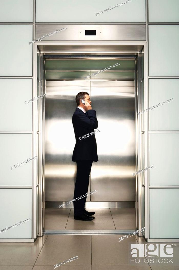 Stock Photo: Businessman Using Cell Phone in Elevator side view.