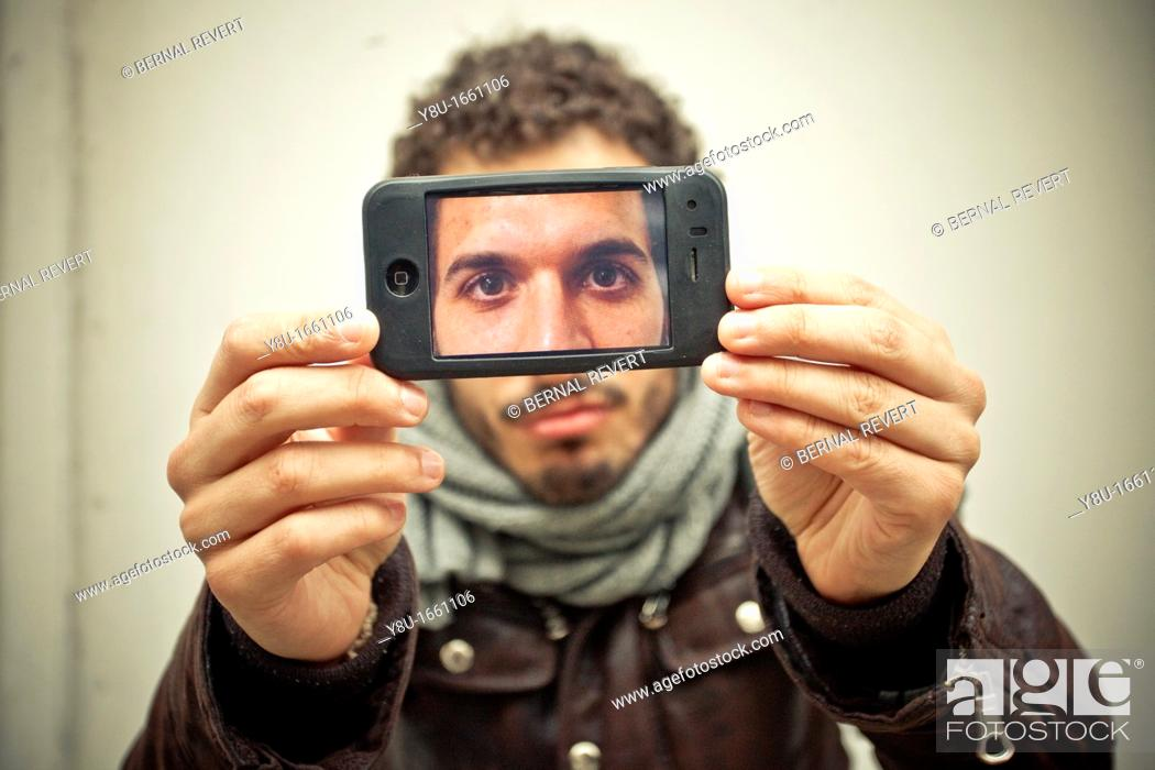 Stock Photo: A young man takes a picture with an iPhone.