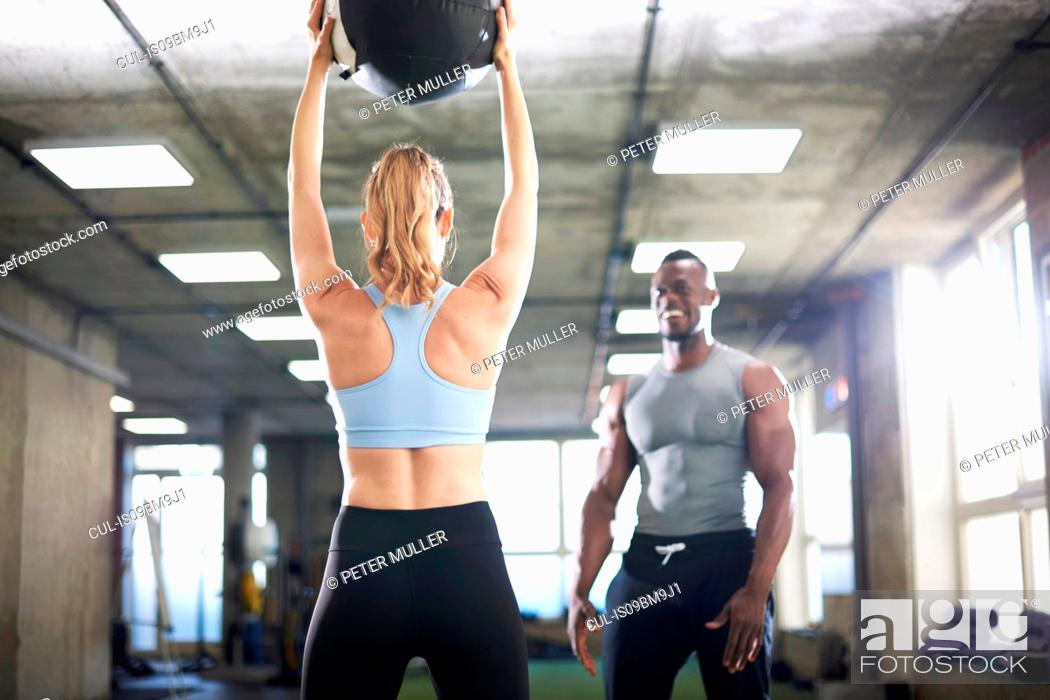 Stock Photo: Trainer watching female client lift medicine ball in gym.