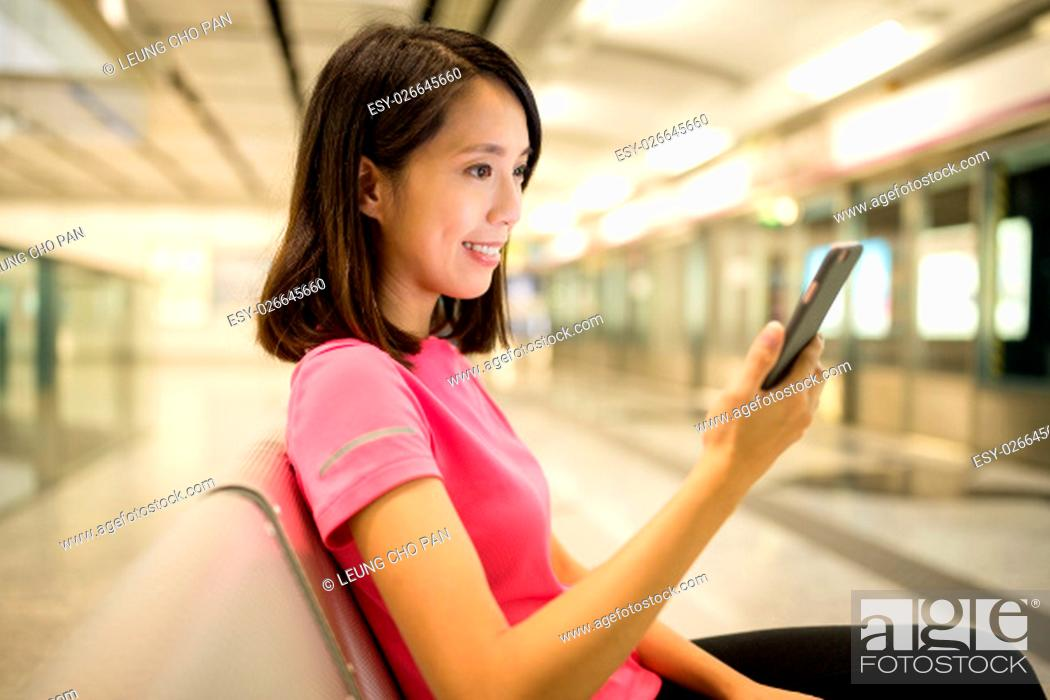 Stock Photo: Woman use of cellphone inside train station.