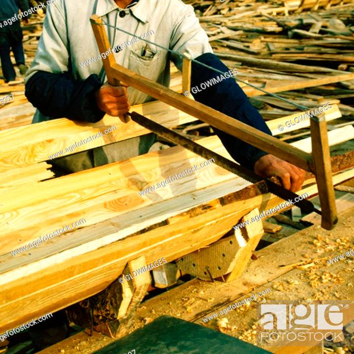 Stock Photo: Mid section view of a carpenter sawing a plank, China.