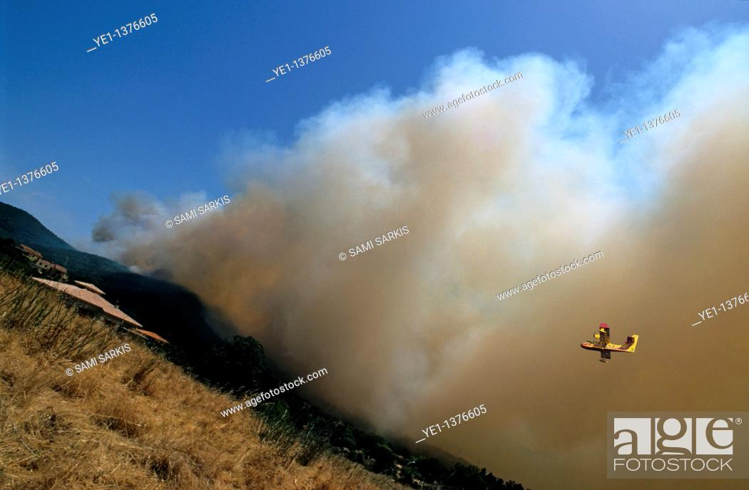 Stock Photo: Heavy smoke from a forest fire travels towards and threatens a house with rescue plane visible in the sky, Propriano, Corsica, France.