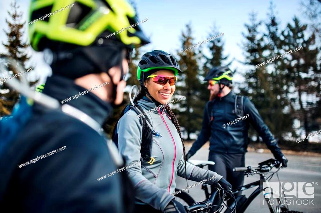 Stock Photo: A group of young mountain bikers standing on road outdoors in winter, talking.