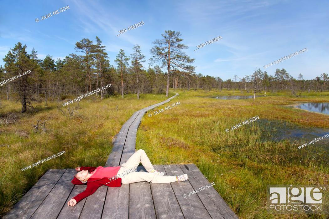Stock Photo: Young Woman Lying on Wooden Boardwalk in Viru Bog, Lääne-Viru County, Estonia, Europe.
