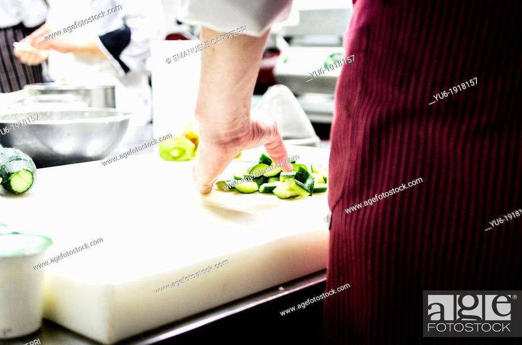 Stock Photo: Cook cutting vegetables in the kitchen.