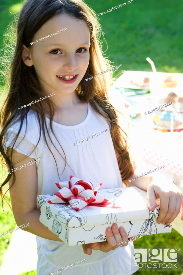 Stock Photo: Girl at birthday party holding wrapped gift.