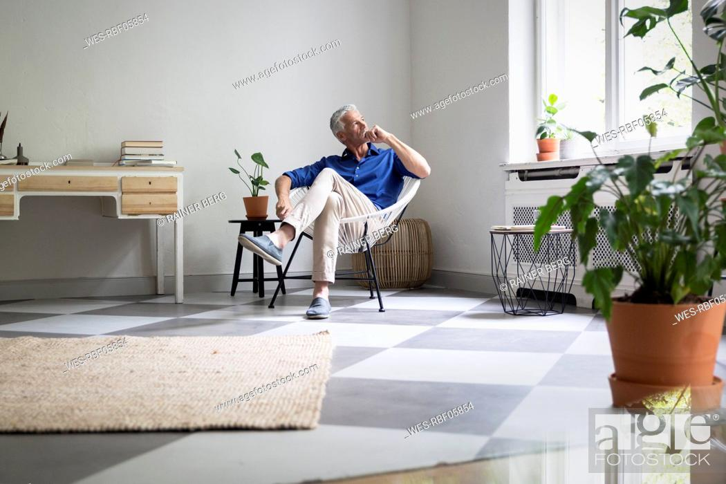 Stock Photo: Mature man sitting at home thinking.