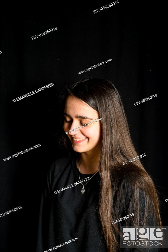 Imagen: portrait of teenage girl with black background -smiling girl with long hair portrait-.