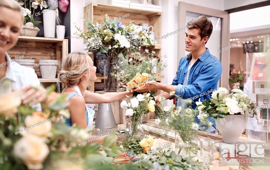 Stock Photo: Florist giving man bouquet at flower shop.