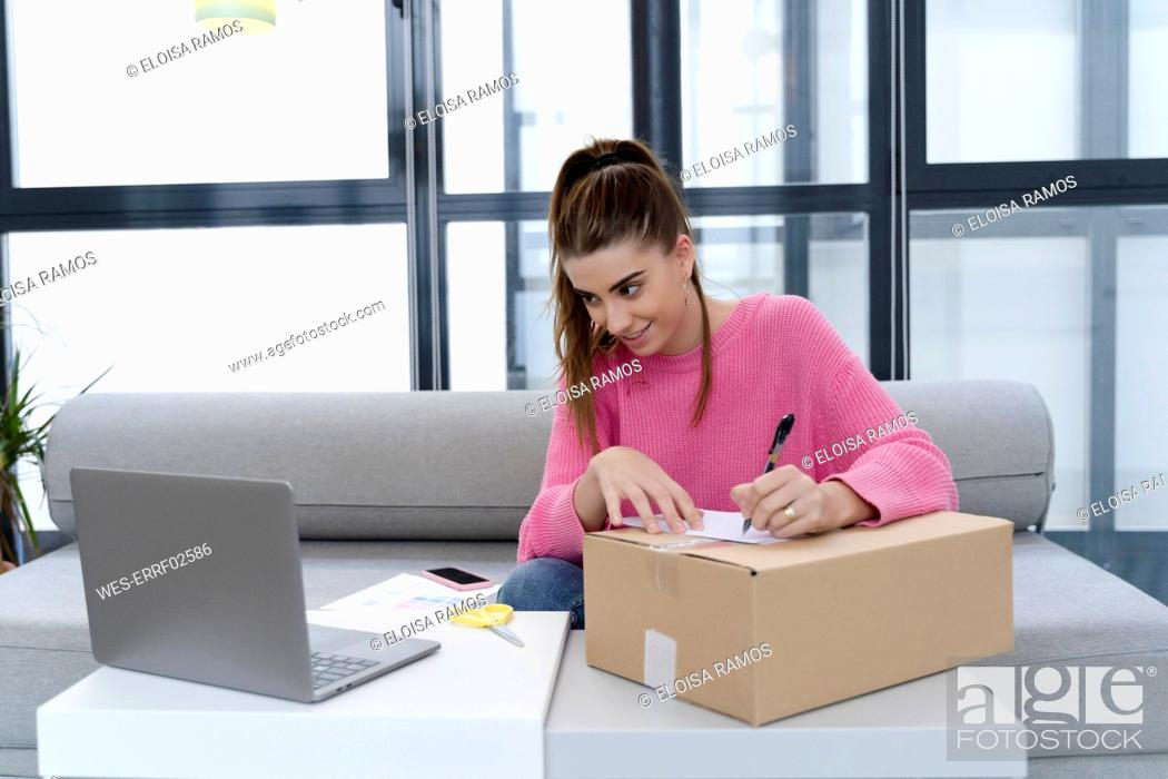 Stock Photo: Young woman sitting on couch preparing parcel for shipping.