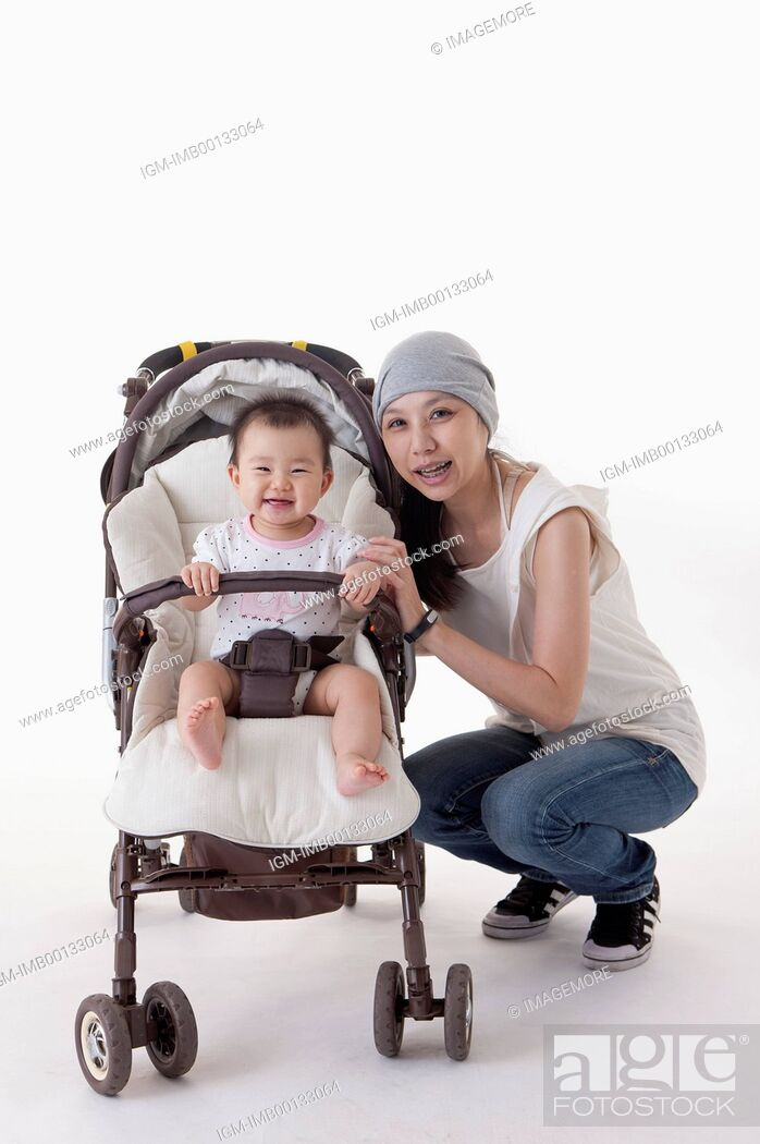 Imagen: Mother crouching near the baby carriage and smiling at the camera,.