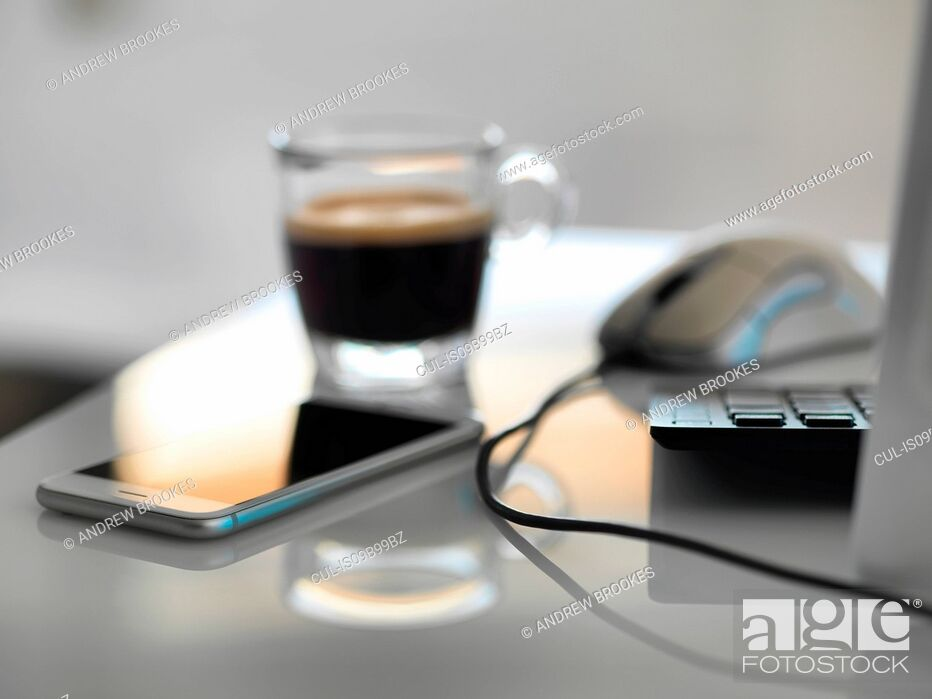 Stock Photo: Morning coffee at office desk with mobile phone and computer.