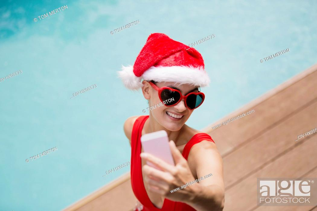 Stock Photo: Playful woman in Santa hat and heart-shape sunglasses taking selfie with camera phone at poolside.