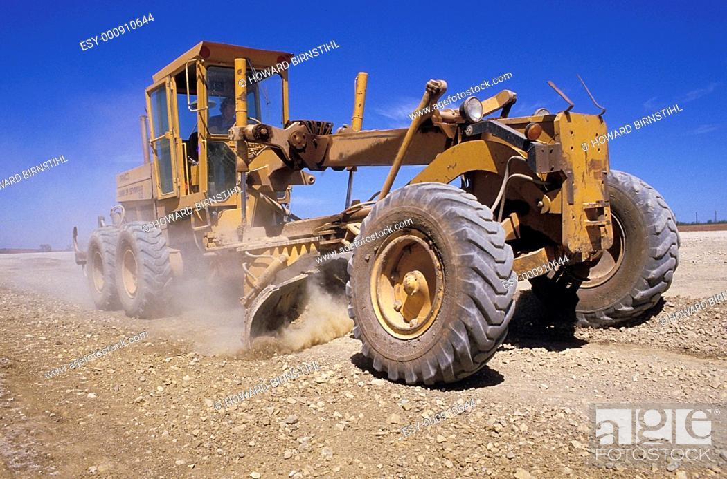 Imagen: large earth mover grading an outback road.