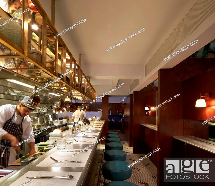 Open kitchen with bar counter seating and chefs at work, Stock Photo ...