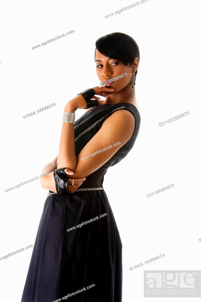 Stock Photo: Beautiful modern classy African American female fashion model in black dress with silver chains and biker gloves looking sideways thinking, isolated.