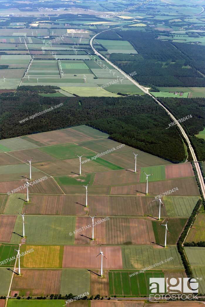 Stock Photo: Aerial view of a windfarm and wind turbines in the middle of agricultural farmland with green fields, forest and a highway passing, Lower Saxonia, Germany.