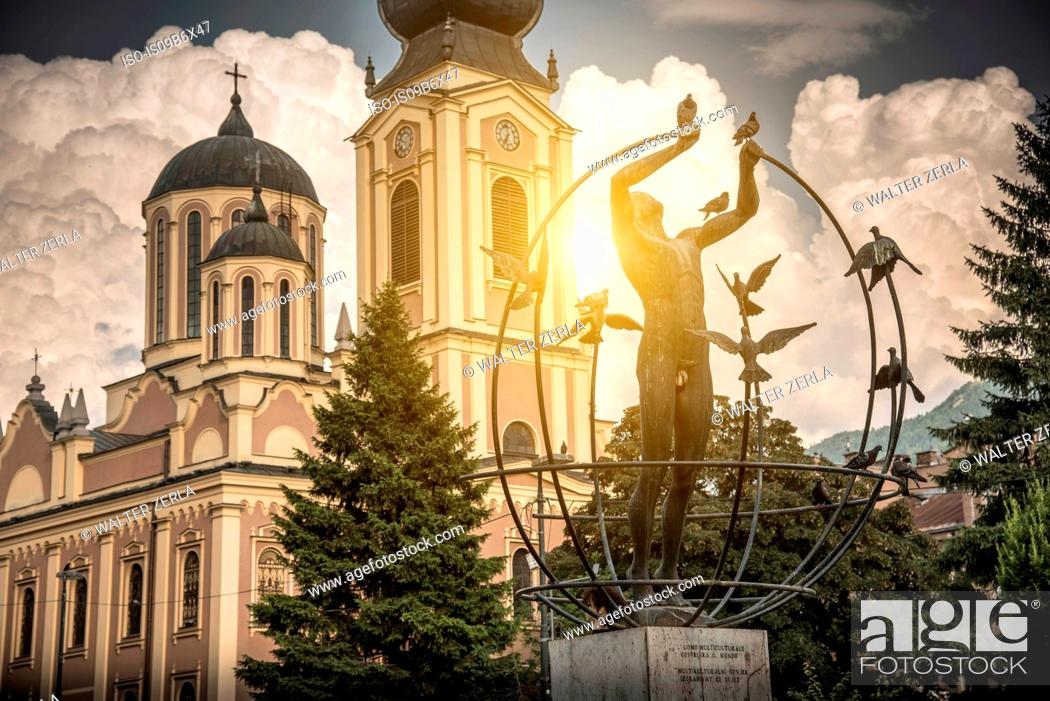 Stock Photo: Multicultural Man Builds the World statue, Serbian Orthodox Cathedral in background, Liberation Square, Sarajevo, Bosnia and Herzegovina.