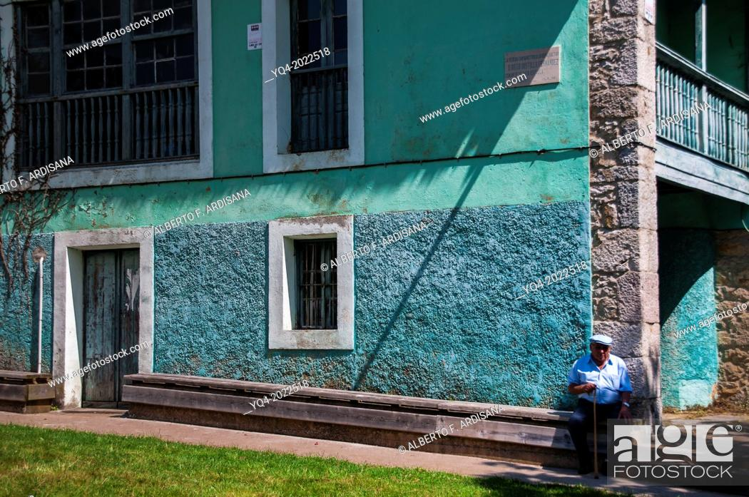 Stock Photo: Man sitting next to a typical house of eastern Asturias. La Pereda. Llanes. Asturias. Spain.