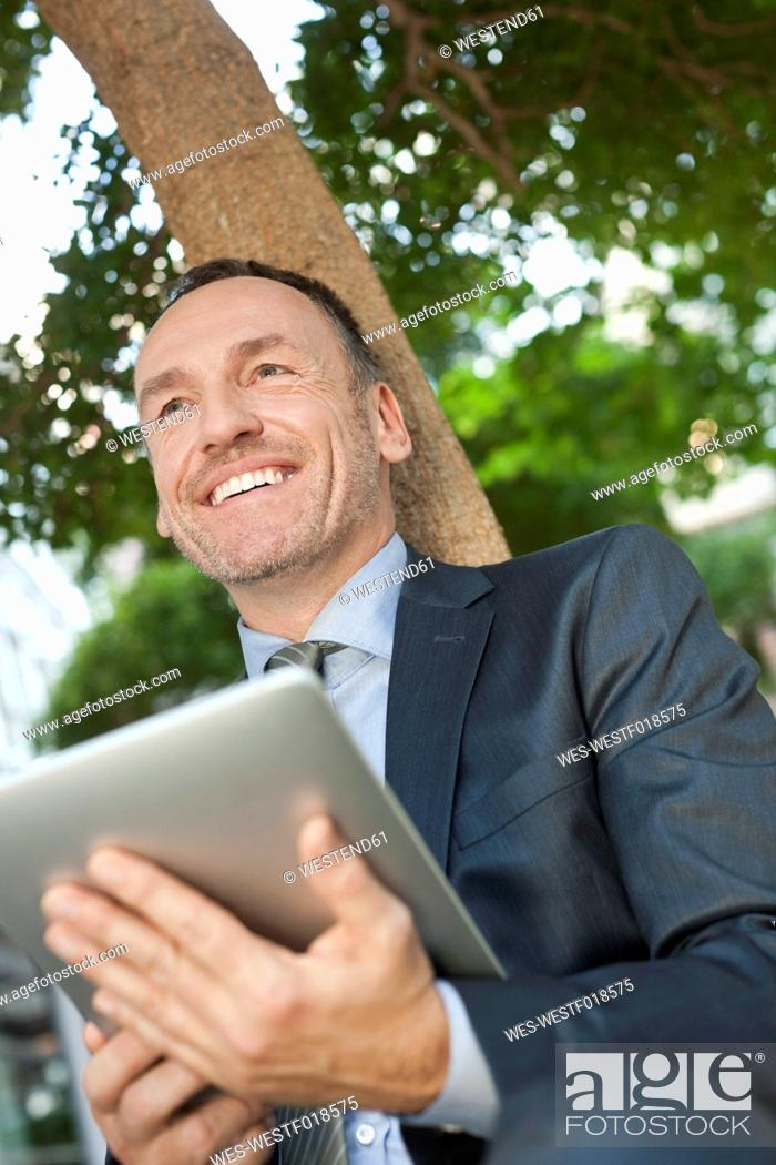 Stock Photo: Germany, Leipzig, Businessman sitting at tree with digital tablet.