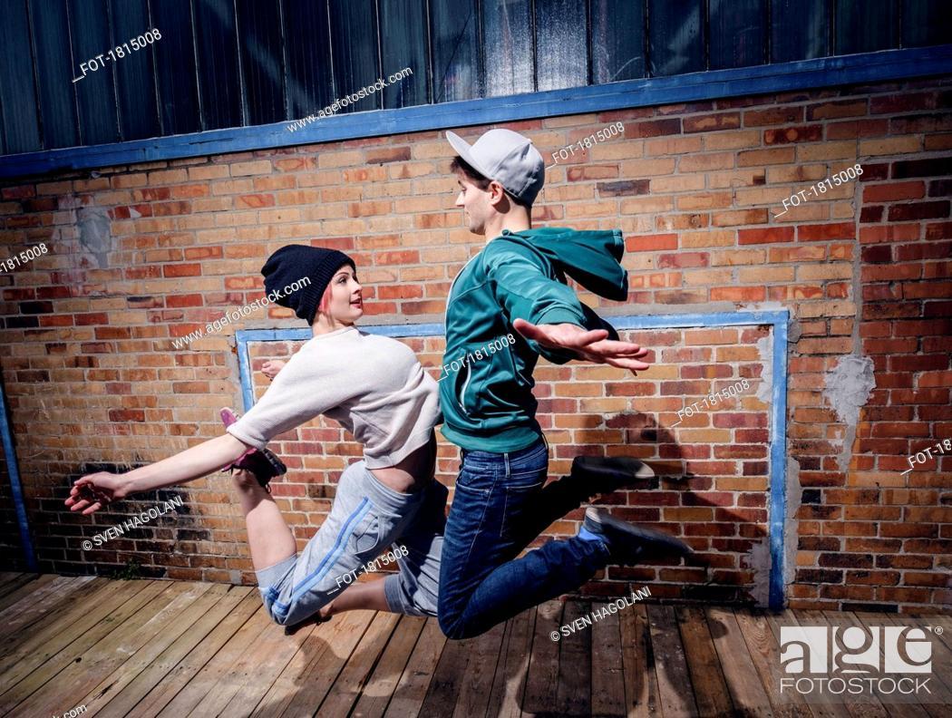 Imagen: Modern dancers performing against brick wall.