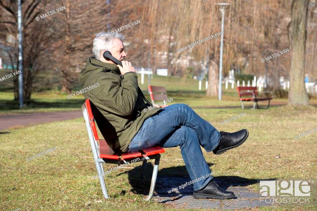Stock Photo: Man sitting on a bench and speaking on the telephone.