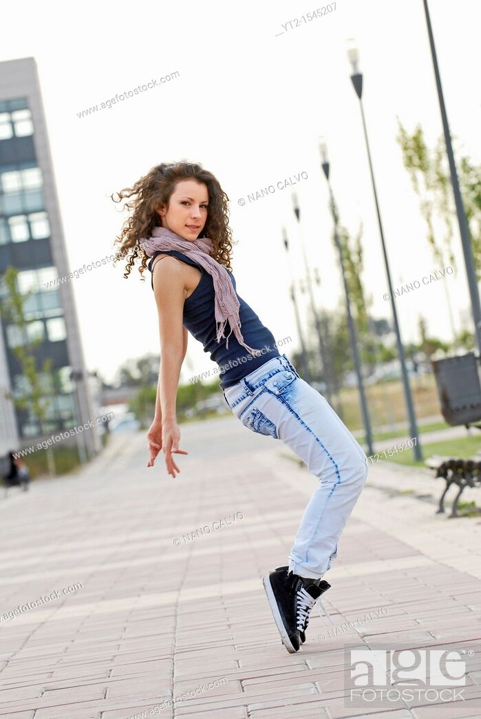 Stock Photo: Cute teen dancer doing a street dance movement.