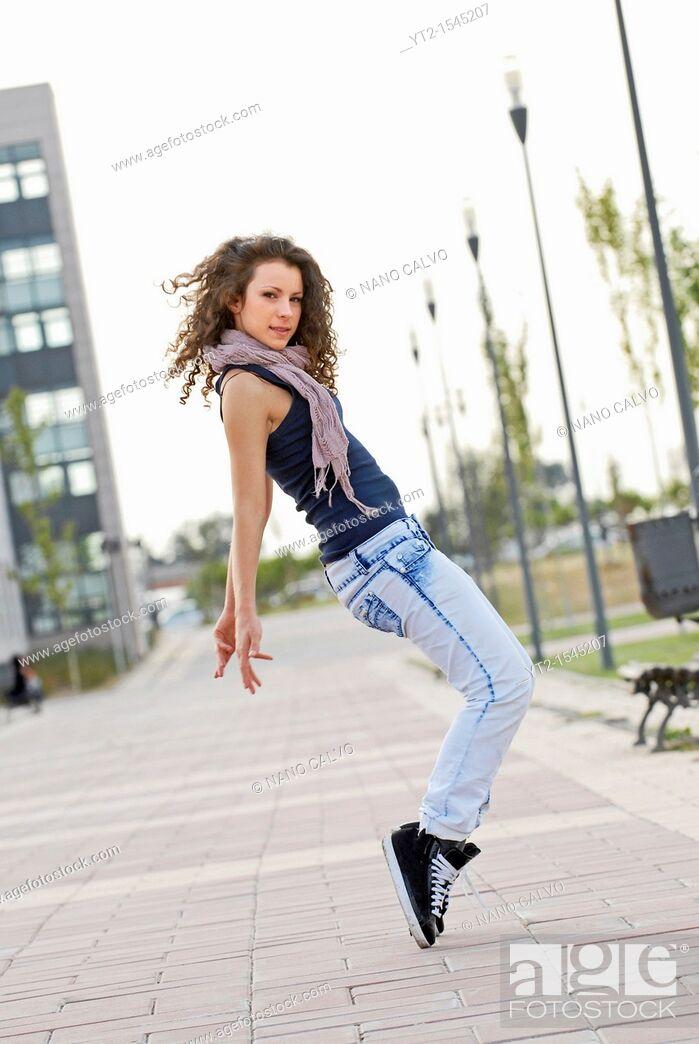 Stock Photo: Cute teen dancer doing a street dance movement.