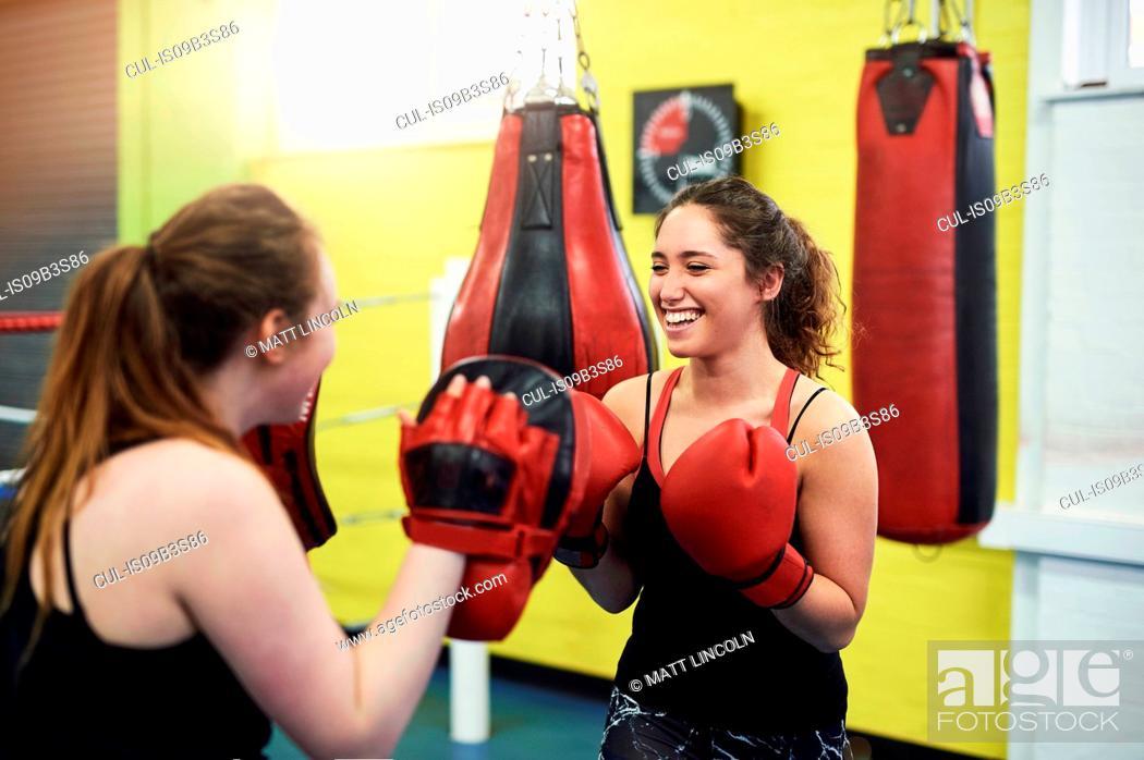 Stock Photo: Female boxer training, punching teammates punch mitt.