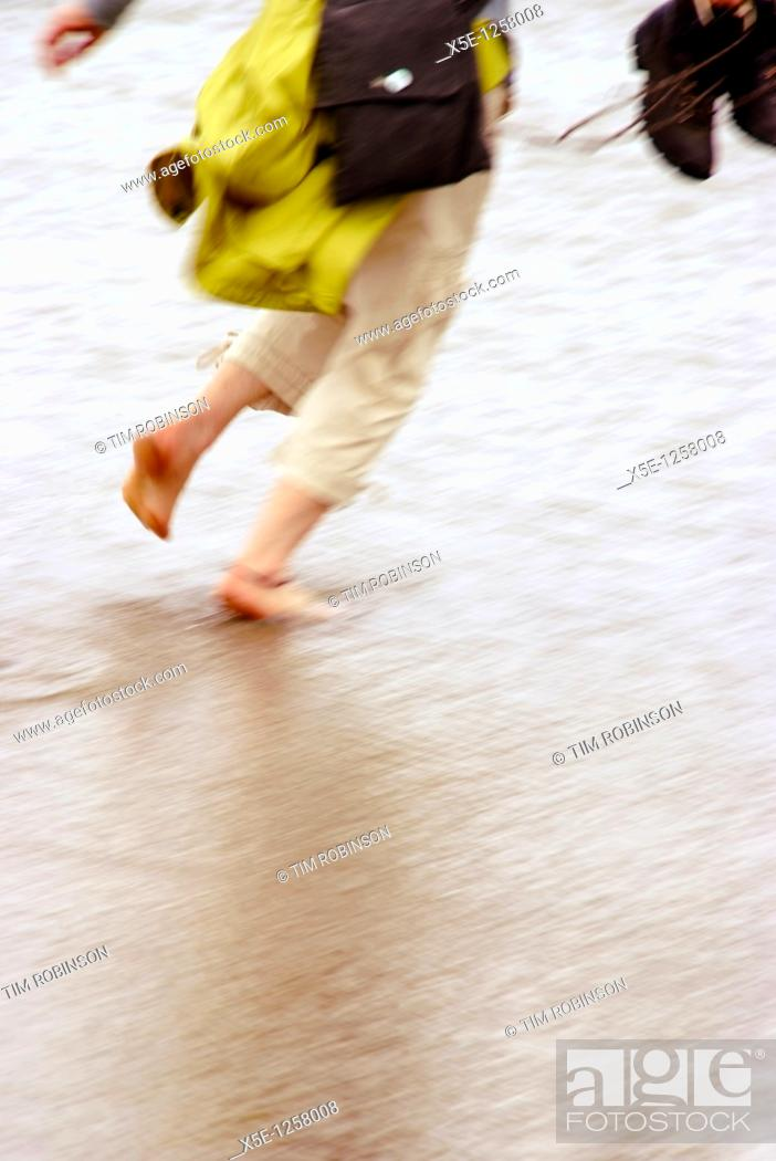 Stock Photo: Legs of young woman running along beach in surf with shoes off.